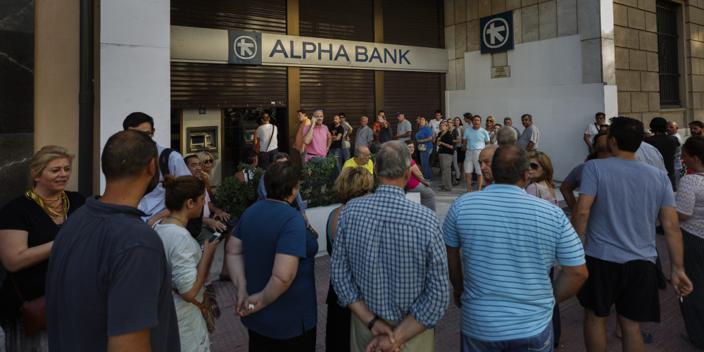 People stand in line Sunday to use a cash machine of a bank in central Athens on Sunday.