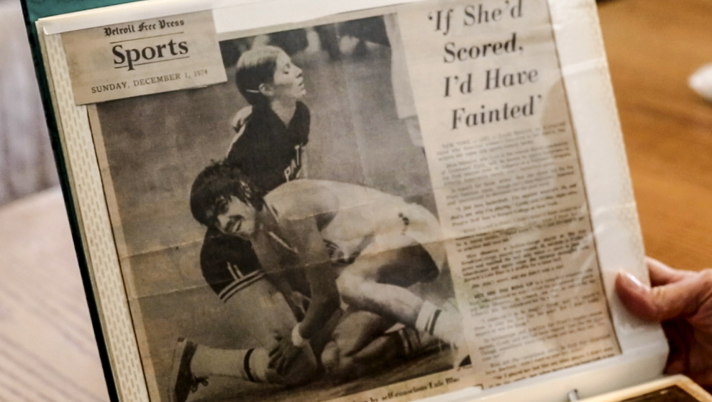 Cyndi Bona holds a news clipping from her time playing basketball at Pratt Institute, where she was the first woman to play men's NCAA basketball.