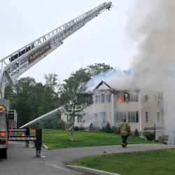 Firefighters work to extinguish flames after a small plane crashed into a house in Plainville, Mass., on Sunday.