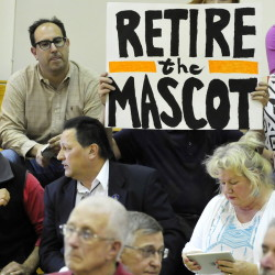 Mark Roman holds a sign calling for the retirement of the Indians nickname for Skowhegan High School sports teams during a forum May 4.
