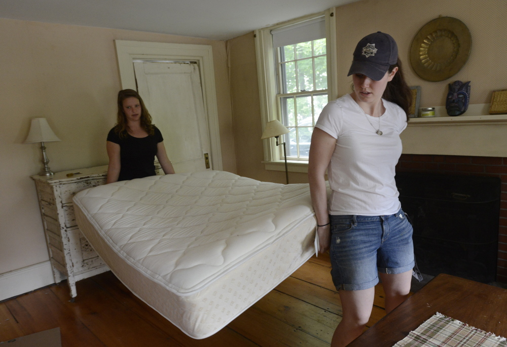 Callie Ferguson, right, carries her mattress out of her apartment  with the help of Eliza Huber-Weiss. Ferguson shared the home with four friends during their senior year at Bowdoin College