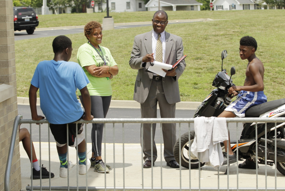 """Community center director Jill Wilson, second from left, and Portland Superintendent Emmanuel """"Manny"""" Caulk speak last week with children in Lexington, Ky., before Caulk was chosen to lead the 40,000-student Fayette County public school system."""