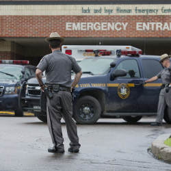 Law enforcement officers stands outside Alice Hyde Medical Center in Malone, N.Y., on Sunday, where David Sweat was taken initially after being shot and captured. He has since been tranferred to Albany Medical Center and his condition has improved.