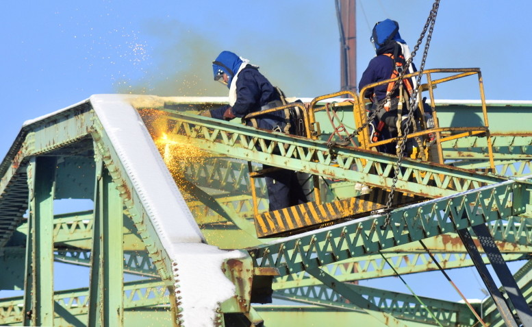 Sparks fly as Reed and Reed Construction workers cut off a piece of the old Richmond-Dresden Bridge on a barge on the Dresden shore of the Kennebec River in January. The same company built the new bridge over the river.