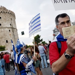 "A supporter of voting ""no"" in the upcoming referendum holds an old 1,000 drachma bank note during a rally in the northern Greek port city of Thessaloniki on Monday. Others fear a return to the drachma would be chaotic."