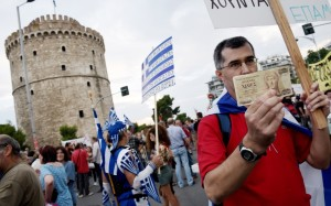 """A supporter of voting """"no"""" in the upcoming referendum holds an old 1,000 drachma bank note during a rally in the northern Greek port city of Thessaloniki on Monday. Others fear a return to the drachma would be chaotic."""