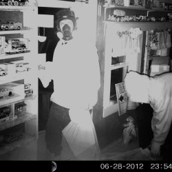 An image from inside a Jay home shows two men, one wearing a gas mask, who stole the owner's coin collection.