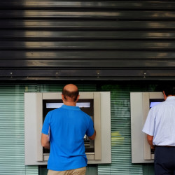 Men use the ATM outside of a closed bank five days before the upcoming referendum, in central Athens, on Tuesday.