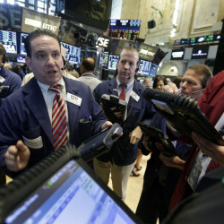 Tommy Kalikas, second left, works with fellow traders on the floor of the New York Stock Exchange on Tuesday.