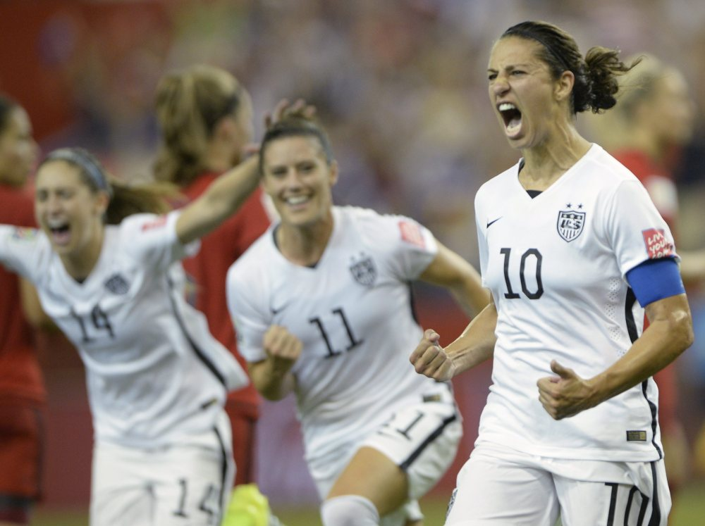The United States' Carli Lloyd (10) celebrates with teammates Ali Krieger (11) and Morgan Brian after scoring on a penalty kick against Germany during the second half of the Women's World Cup semifinal match Tuesday night in Montreal.