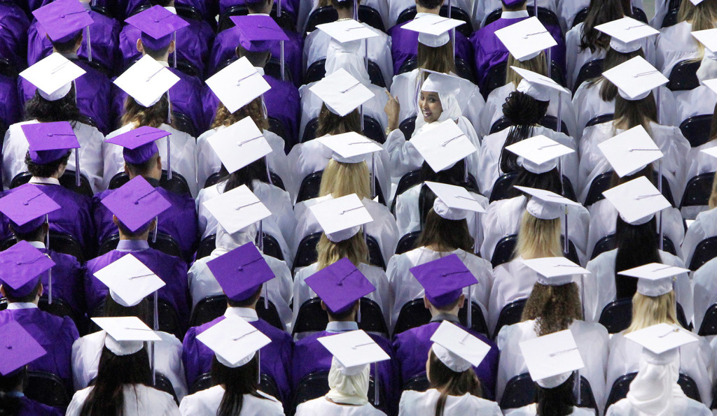 Deering High School senior Sundus Mohamed glances behind at the start of Deering's graduation at the Cross Insurance Arena in Portland on Wednesday.