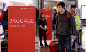 Travelers walk toward the baggage drop area for Delta airlines at Seattle-Tacoma International Airport in March. This summer travel season, Delta plans to preload carry-on bags above passengers' seats on some flights.  The Associated Press