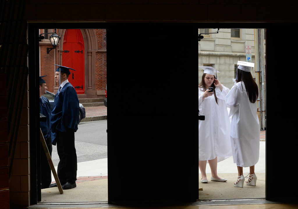 Liam Densmore, seen through the left door, and and Montana Sangillo and Mica Rodriguez, seen at right, catch some fresh air outside the Portland High School gym while waiting for the start of the school's 194th graduation exercises at Merrill Auditorium in Portland on Thursday.