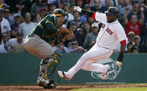 Red Sox DH David Ortiz scores on a single by Mike Napoli as Athletics catcher Stephen Vogt bobbles the throw in the third inning Saturday at Fenway Park. The Associated Press