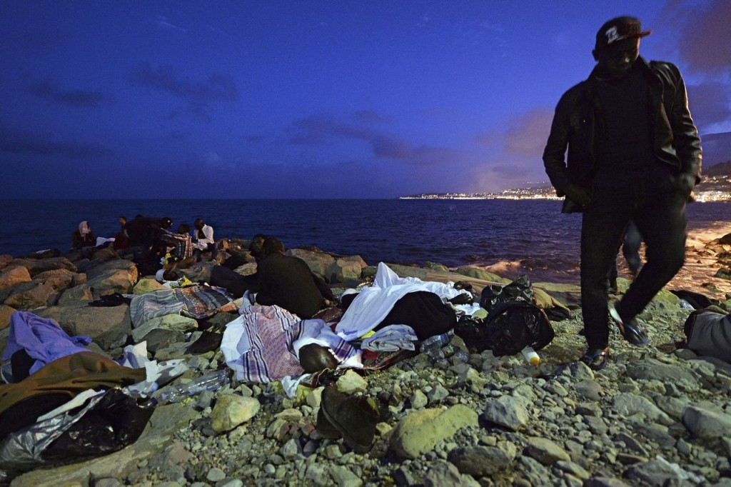 Migrants sleep on the rocks by the sea in Ventimiglia, at the border between Italy and France, early Monday. The Associated Press