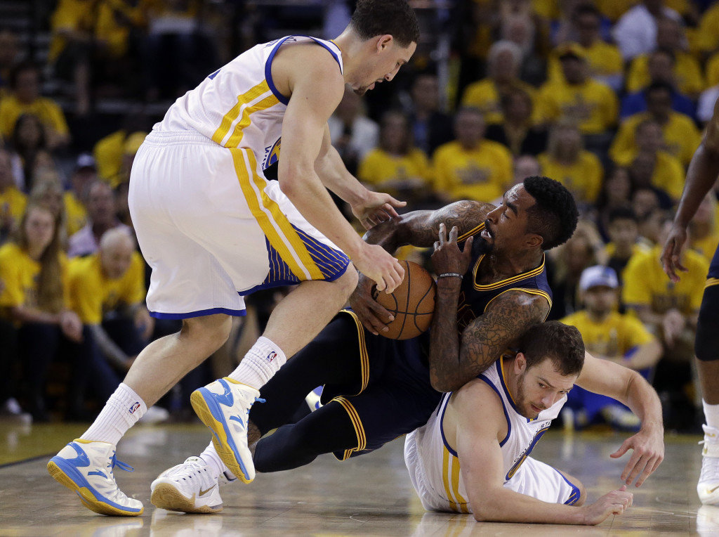 Cavaliers guard J.R. Smith falls on top of Golden State's David Lee while Klay Thompson moves in to try to take the ball away. Golden State is one win away from its first NBA title since 1975 and can clinch the series Tuesday night. The Associated Press