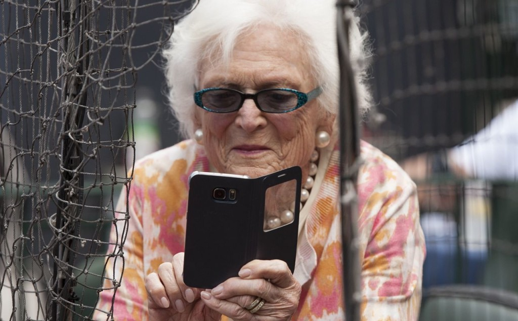 Former first lady Barbara Bush takes photos with her cellphone before  a Houston Astros game in Houston in this May 3, 2015, photo.
