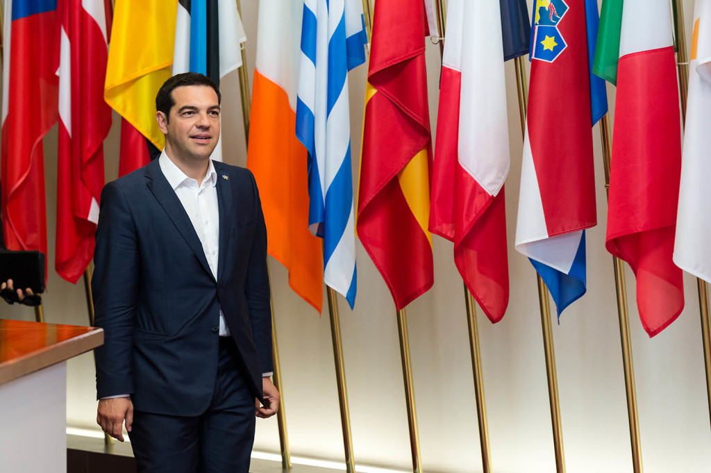 Greek Prime Minister Alexis Tsipras walks in front of European flags after a meeting with European Commission President Jean-Claude Juncker on the sidelines of the EU meetings in Brussels on Thursday. Tsipras continued his diplomatic offensive, meeting with EU ministers as Greece strives to avoid bankruptcy. The Associated Press