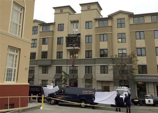 Police and officials stand outside of the Library Gardens apartment complex, where a fourth floor balcony rests on the balcony below after collapsing early Tuesday morning near the University of California, Berkeley. The Associated Press