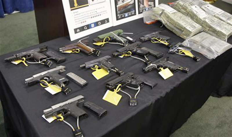 Weapons and money collected during a gang roundup are displayed at a news conference Thursday in Boston. The Associated Press