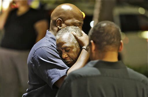Worshippers embrace following a group prayer across the street from the scene of a shooting Wednesday, at Emanuel AME Church in Charleston, S.C. The Associated Press