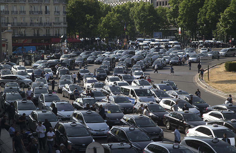 Taxis block a major entrance to Paris in protest over Uber.