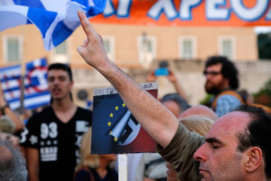 "A supporter of a ""no"" vote in the upcoming referendum on creditors' economic proposals makes the victory sign during a rally at Syntagma Square in Athens on Monday. The July 5 referendum could determine whether the country has to ditch the euro currency and return to the drachma."