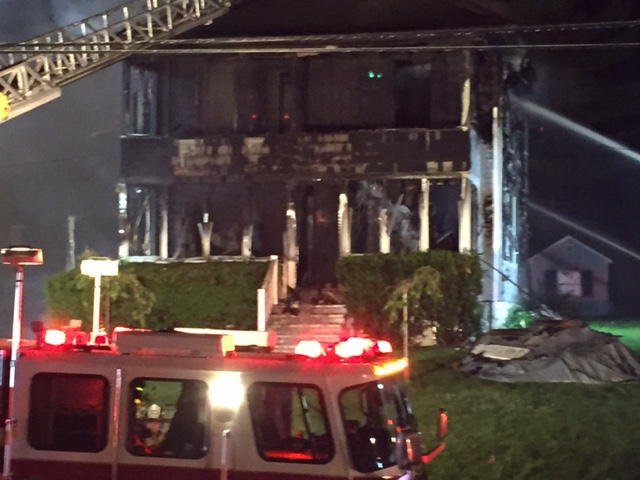 Firefighters fight the blaze Friday night at a multi-unit home on Pierce Street in Westbrook. Edward D. Murphy photo