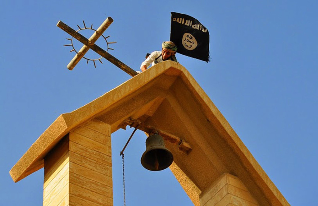 In this photo released March 7 by a militant website, a member of the Islamic State group holds the ISIS flag as he dismantles a cross on the top of a church in Mosul, Iraq. The Associated Press