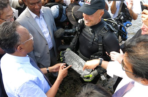 Underwater explorer Barry Clifford presents a silver bar he believes is part of the treasure of the pirate Captain Kidd, to the president of Madagascar, Hery Rajaonarimampianina, left, on Sainte Marie Island, Madagascar, in this May, 7, 2015, photo.