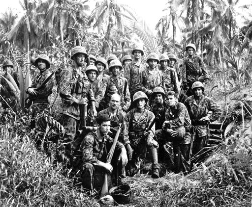 This January, 1944,  photo shows U.S. Marine Raiders posing in front of a Japanese stronghold they conquered at Cape Totkina, Bougainville, in the Solomon Islands. The Associated Press