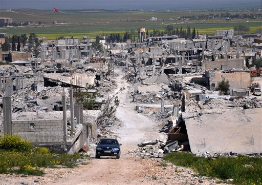 In this April 18, 2015, photo a car passes through an area of Kobani that was destroyed during the battle between U.S. backed Kurdish forces and  Islamic State fighters. Turkish officials say the Islamic State group has staged a new attack to retake Kobani. The Associated Press