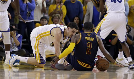 Cleveland guard Kyrie Irving tries to control the ball next to Golden State guard Klay Thompson during overtime of Game 1 of the NBA Finals in Oakland, Calif., on Thursday. Irving left the game with a fractured left kneecap right after this play. The Associated Press