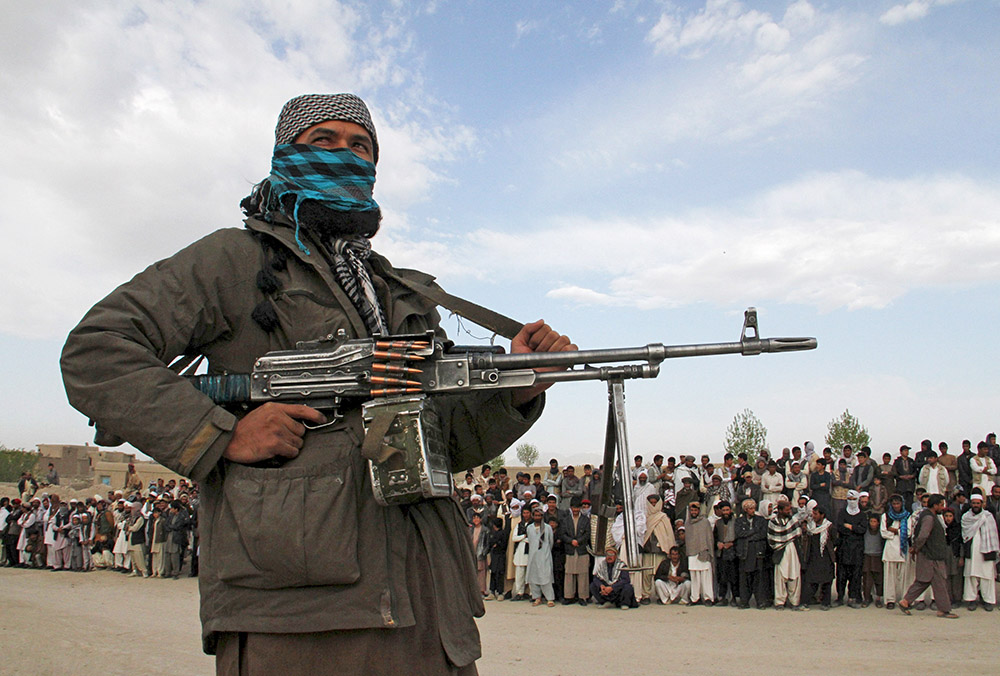 A member of the Taliban stands guard where the execution of three men took place on April 18, 2015. Former Taliban fighters now loyal to the Islamic State control the district of Kot, say tribal elders and provincial officials. Reuters