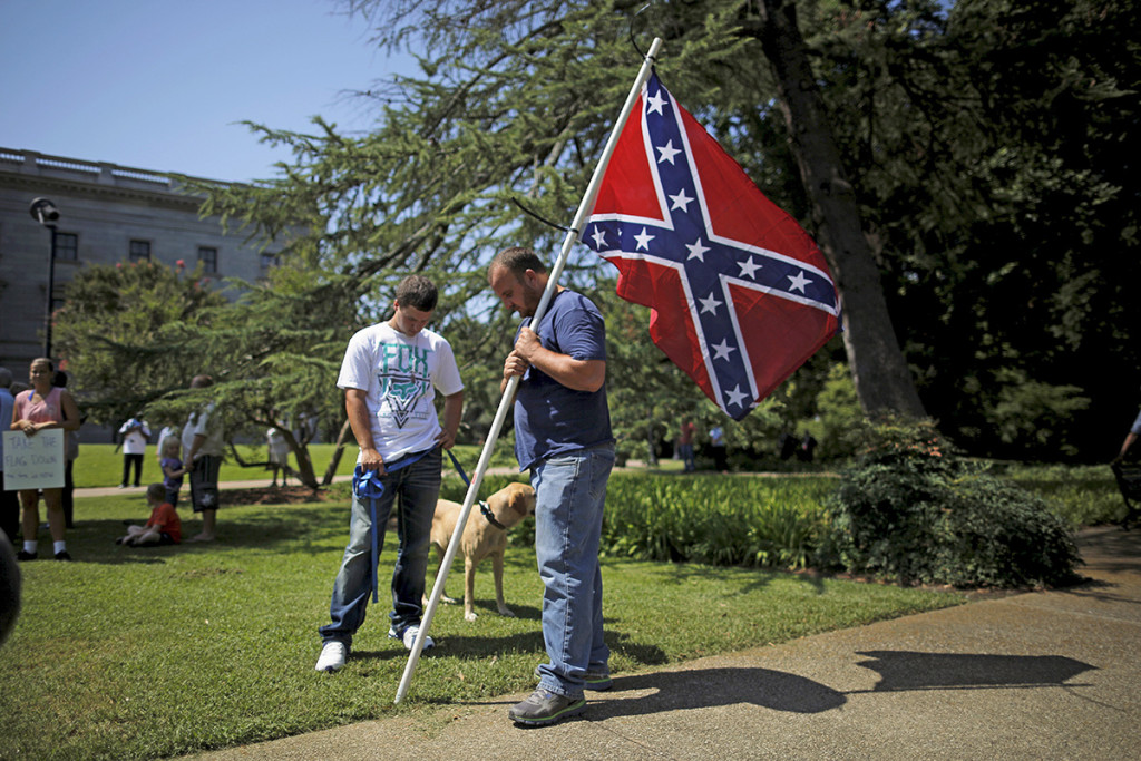 A man, who declined to give his name, holds a Confederate flag during a rally outside the South Carolina Statehouse on Tuesday. Lawmakers planned to introduce a resolution to begin a debate on removing the Confederate flag from the Statehouse grounds. Reuters