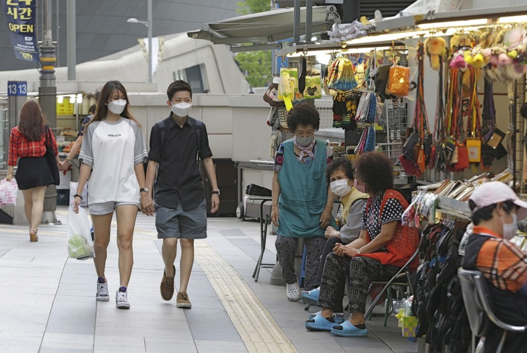 A couple wears masks as a precaution against MERS – Middle East Respiratory Syndrome – at a market in Seoul, South Korea, Thursday. The Associated Press