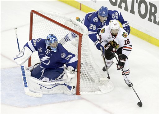 Chicago Blackhawks center Marcus Kruger wraps the puck around the goal in an attempt to score against Tampa Bay Lightning goalie Ben Bishop as Matt Carle helps defend in the third period of Game 5 of the Stanley Cup finals on Saturday in Tampa, Fla. The Associated Press