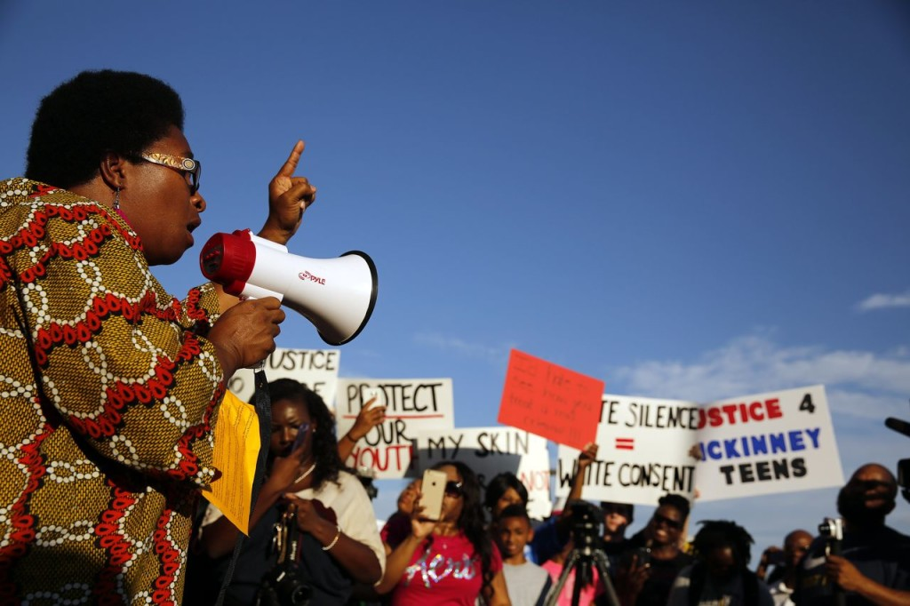 Olinka Green, founder of No Longer Invisible, leads a protest at Joyce Kelley Comstock Elementary School on, Monday before marching to the Craig Ranch pool where McKinney Police Cpl. Eric Casebolt was  seen on video pinning an African-American girl to the ground and pointing his gun at other teenagers.The Dallas Morning News via AP