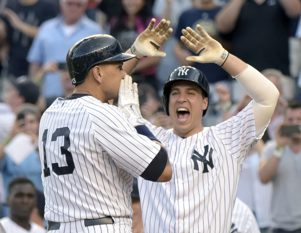 Alex Rodriguez (13) celebrates with Mark Teixeira after hitting a home run in the first inning Friday against the Detroit Tigers. The home run was his 3,000th career hit. The Associated Press