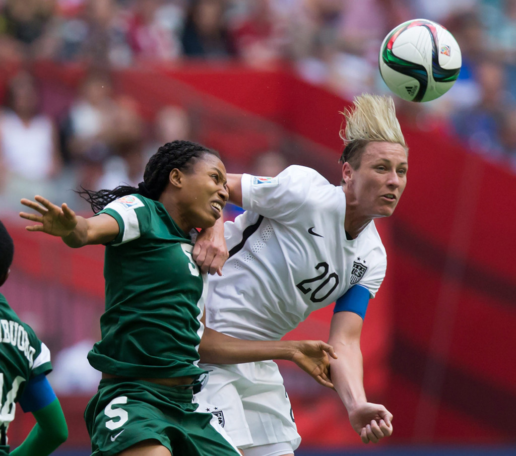 Nigeria's Onome Ebi, left, and United States' Abby Wambach vie for the ball during the second half of a FIFA Women's World Cup soccer game Tuesday  in Vancouver, British Columbia, Canada. The Associated Press