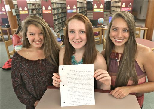"""High school students Mollykate Rodenbush, left, Brittany Tainsh and Michaela Arguin hold a letter from former Boston crime boss James """"Whitey"""" Bulger in Lakeville, Mass. The three Apponequet Regional High School students wrote to Bulger for a history contest on leadership and got a surprising letter back. David L Ryan/The Boston Globe via AP"""