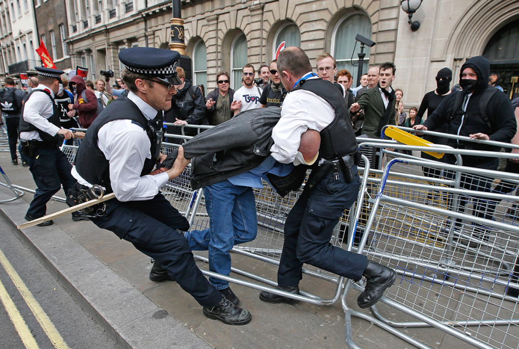 Police officers grapple with a demonstrator during protest outside Parliament in central London on  May 27, 2015. As increasingly horrified British officers and commanders have watched videos of American cops firing on civilians, they say they hope that some of their strategies and practices can be translated across the Atlantic. Reuters