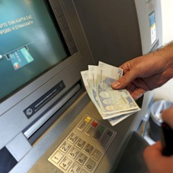 A man withdraws 60 euros, the maximum amount allowed after the imposed capital controls in Greek banks, at a National Bank of Greece ATM in Piraeus port near Athens Tuesday. The head of the European Commission made a last-minute offer to try to persuade Greek Prime Minister Alexis Tsipras to accept a bailout deal he has rejected before a referendum on Sunday that EU partners say will be a choice of whether to stay in the euro. Reuters