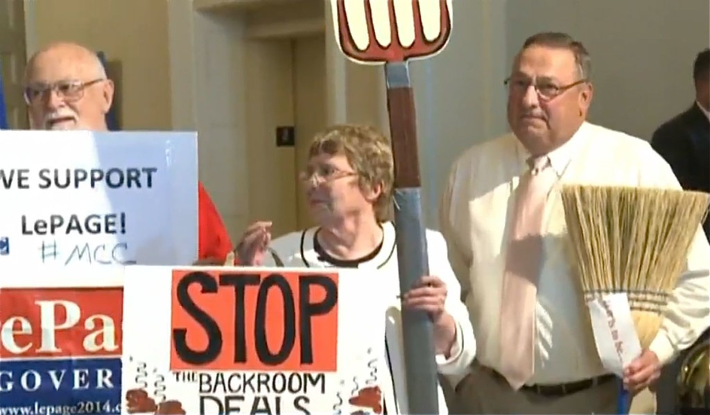 Gov. Paul LePage holds a broom during a rally of about 50 people who supported the governor's veto of the $6.7 billion state budget. The governor said the broom represented his conviction that he had been re-elected to clean up in Augusta. Screen image from WCSH-TV video