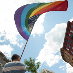 A gay marriage supporter carries a gay pride American flag in Bangor after the U.S. Supreme Court ruling upholding gay marriage in June. A national anti-gay marriage group has lost another round in its attempt to hide the identities of donors to a successful 2009 referendum campaign to reverse Maine's marriage equality law.