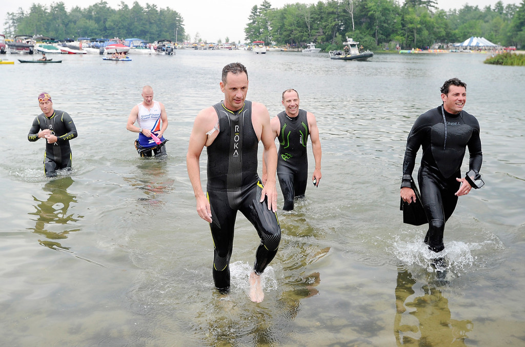 Five Navy SEALs emerge from Sebago Lake as they complete the Summit to Sunshine Challenge, a reverse triathlon, at Point Sebago Resort on Thursday.