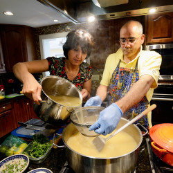 Tasneem and Dr. Rifat Zaidi drain the broth into the main dish while preparing haleem. The family expresses faith by sharing this traditional Pakistani dish to observe Ramadan.