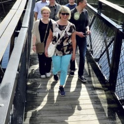 A group from Kotlas, Russia, sister city to Waterville, crosses the Two-Cent Bridge during their tour of the city Tuesday. The group arrived Friday and will leave later this week.