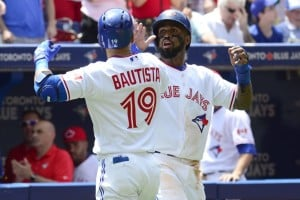 Jose Bautista is congratulated by teammate Toronto  Jose Reyes after hitting a two-run home run against the Boston Red Sox during the second inning of a baseball game in Toronto on Wednesday, July 1, 2015.
