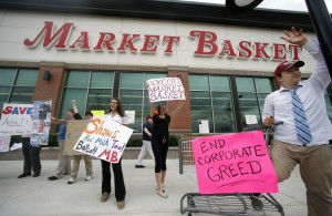 Market Basket employees Rees Gemmell, far right, and colleagues acknowledge passing supporters as they picket in front of the Haverhill, Mass., store in July 2014.